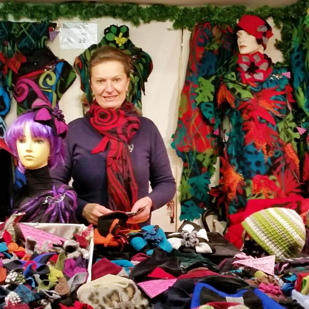 Adeline Schoden steht in Ihrem Weihnachtsmarkt Stand, umringt von Ihren Kleidungstücken.