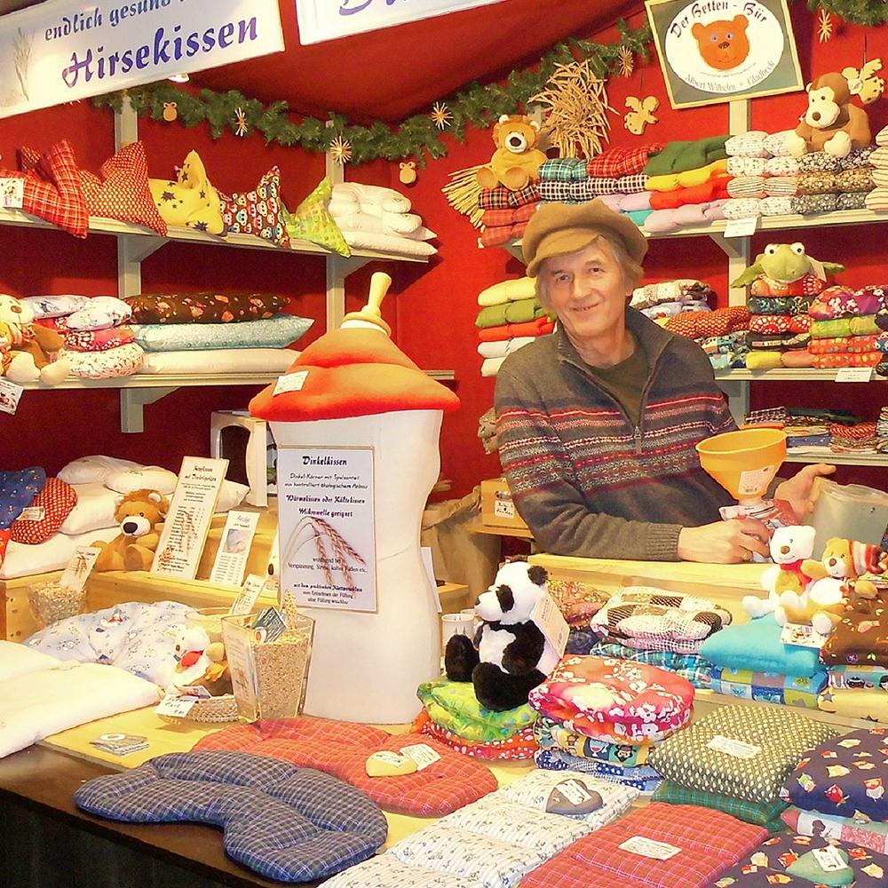 Der Verkäufer steht umgeben von seinen Erzeugnissen- Kissen.