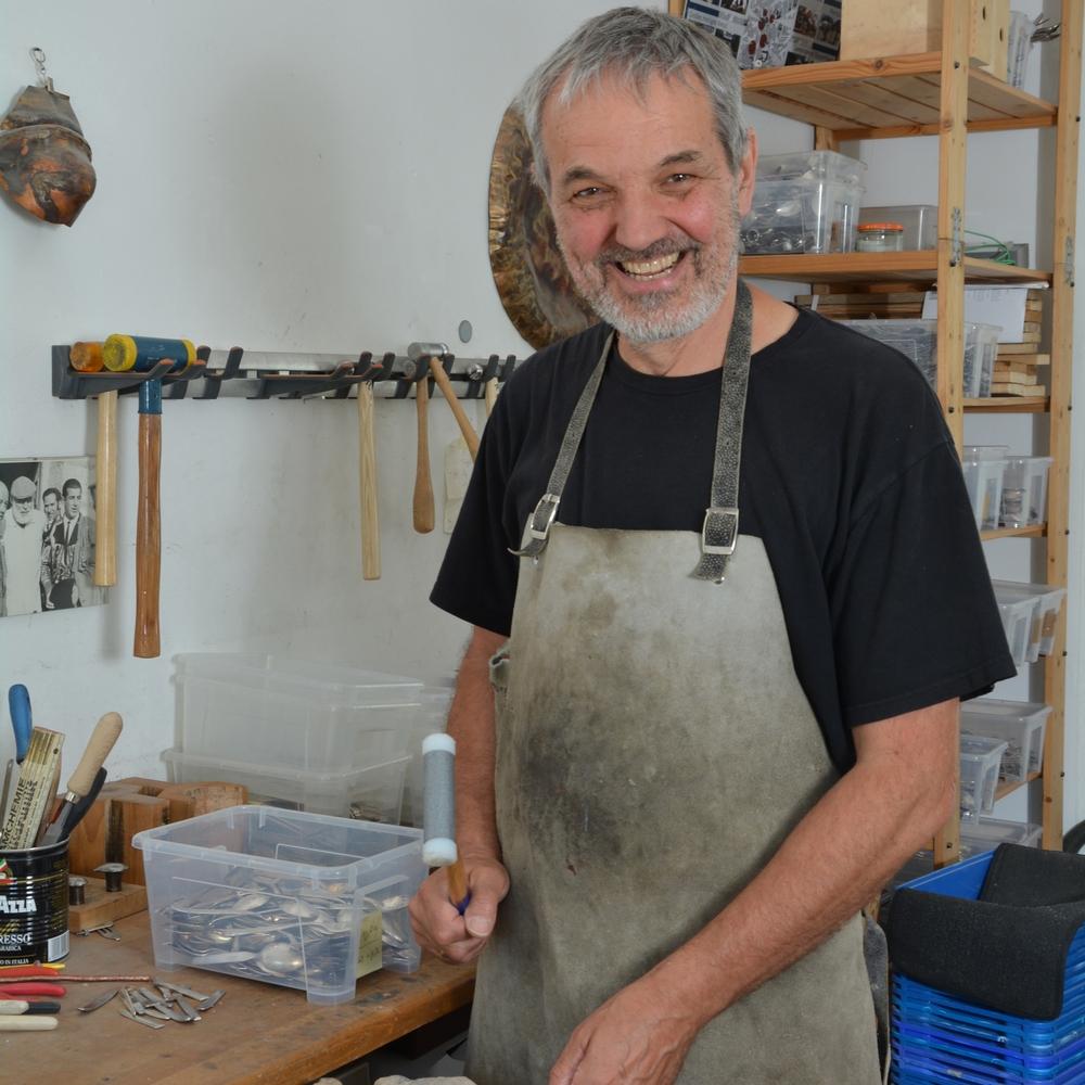 Ein Mann stellt in seiner Werkstatt einen Holzartikel her.