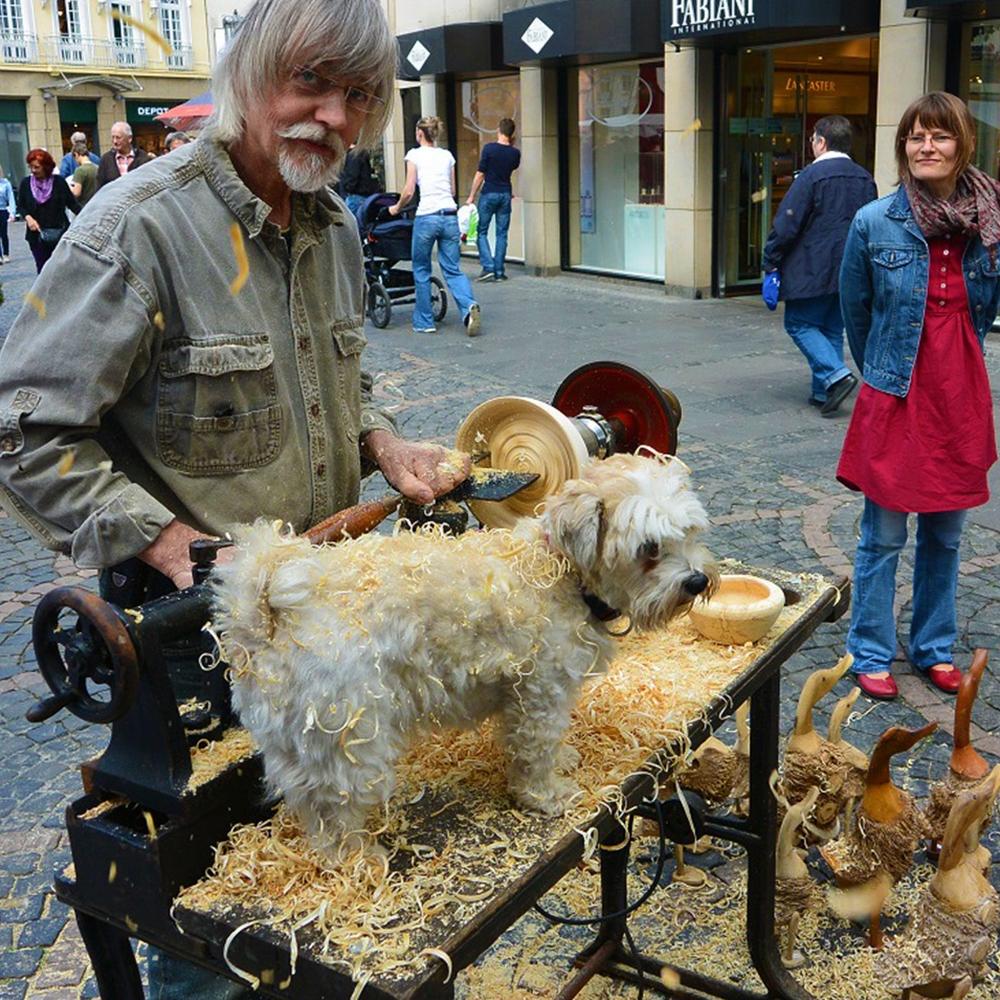 Auf der Werkbank auf dem Bonner Weihnachtsmarkt steht ein Hund, Sägespähne liegen auf seinem Fell.