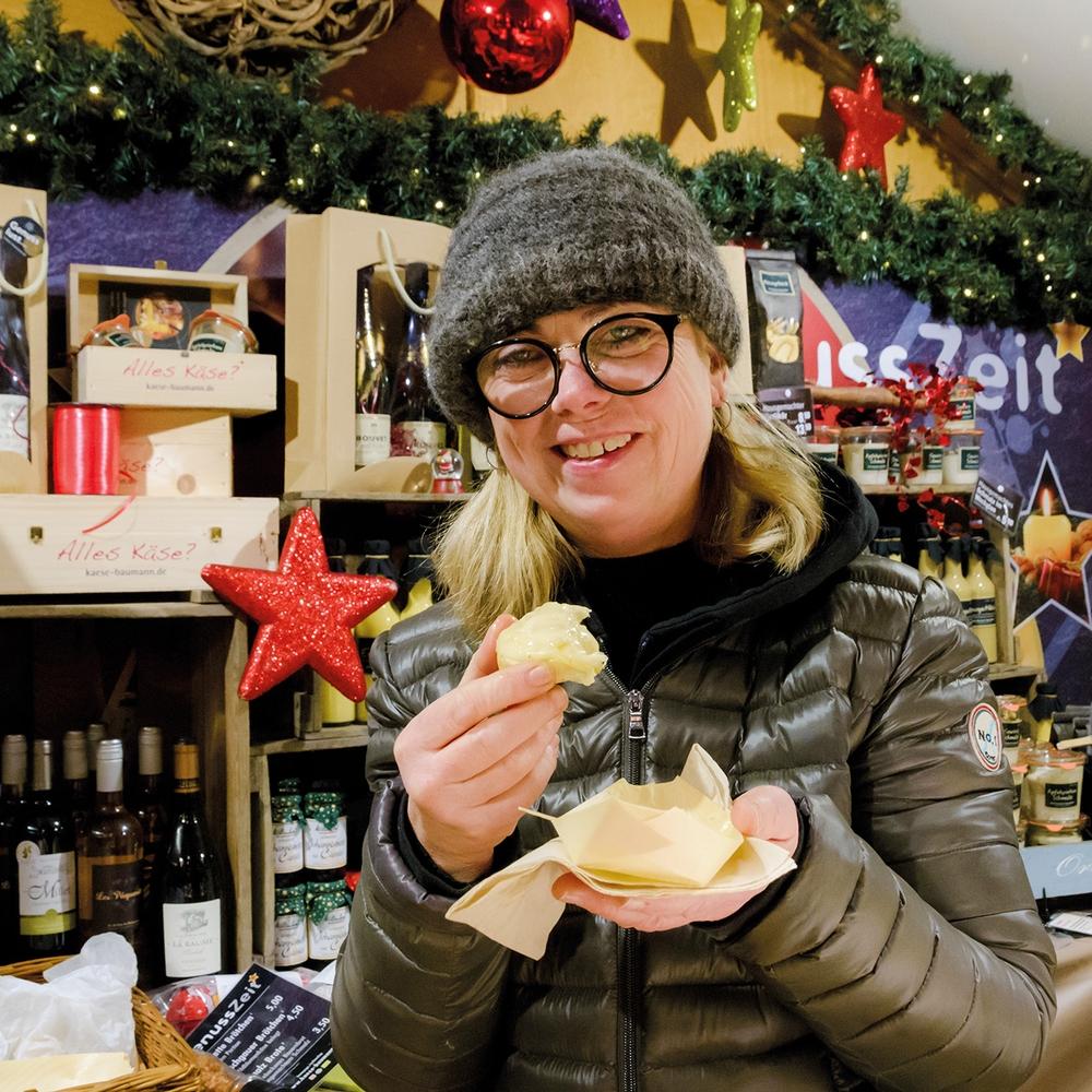 Die Frau steht am Weihnachtsstand mit Käse, umgeben von Weihnachtsdekoration- und Artikeln