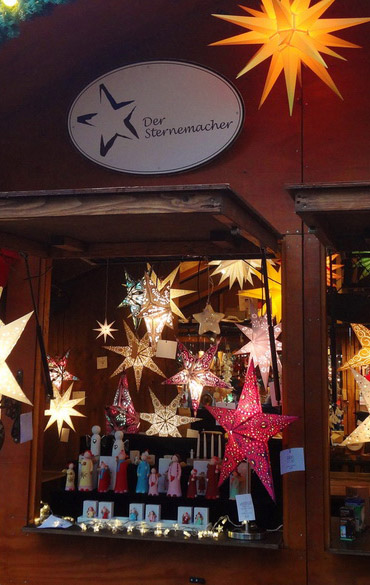 Standluke mit beleuchteten Weihnachsternen und Holzfiguren