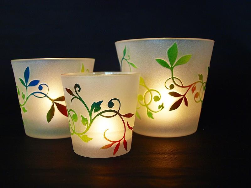 Mit Blattmotiv versehene unterschiedlich große Teelichtgläser bzw. Teelichtglas