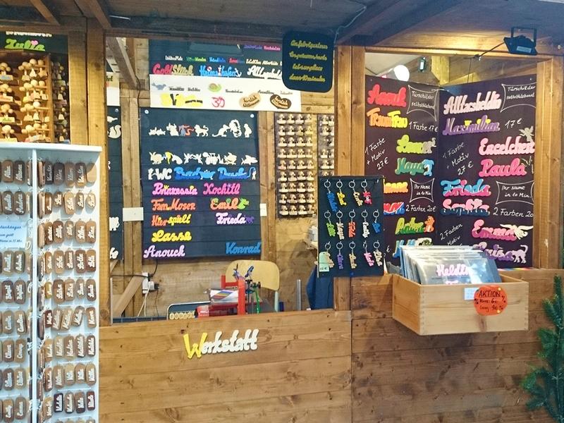 Werkstatt-Arbeitsplatz mit Dekupiersäge direkt auf dem Bonner Weihnachtsmarkt Stand mitsamt den gefertigten Namen aus Holz und anderen Holzwaren