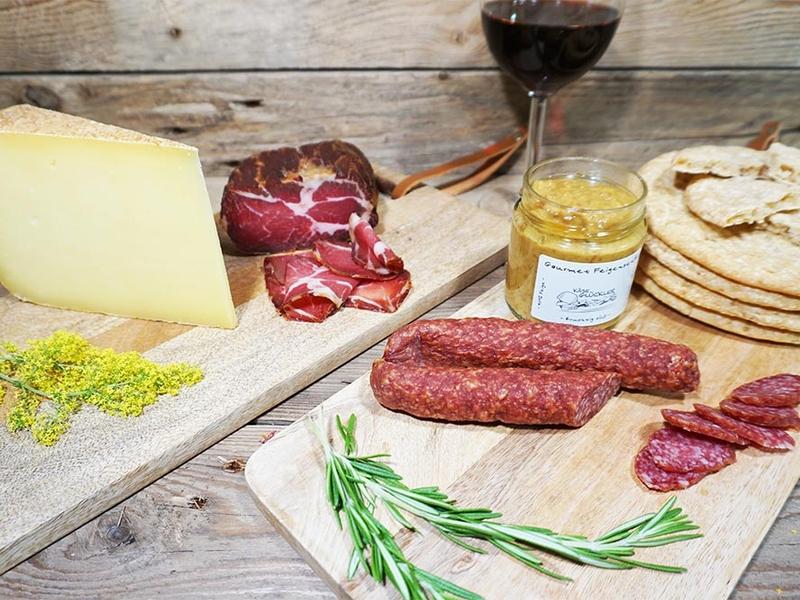 Genusspaket mit Karminwurz, Bergkäse, Tiroler Schinken, selbstgemachtem Gewürzbrot Schüttelbrot und feinstem Senf. Alles appetitlich zur Jause angerichtet