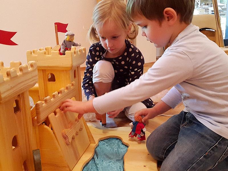 Begeisterte Kinder beim Spielen mit Holzburg